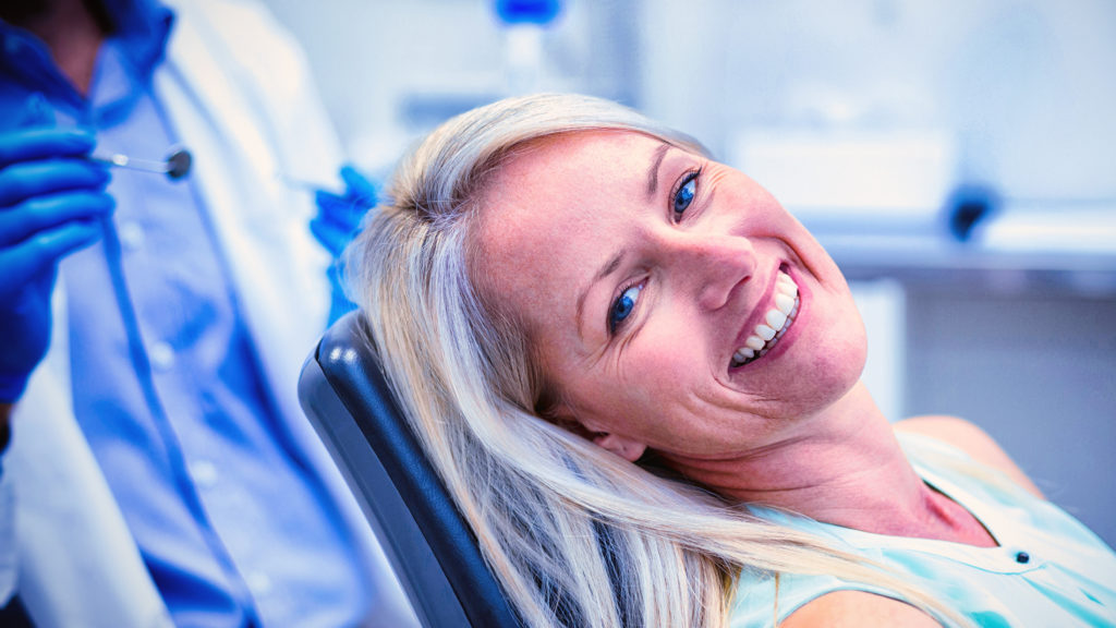 woman getting implant secured dentures
