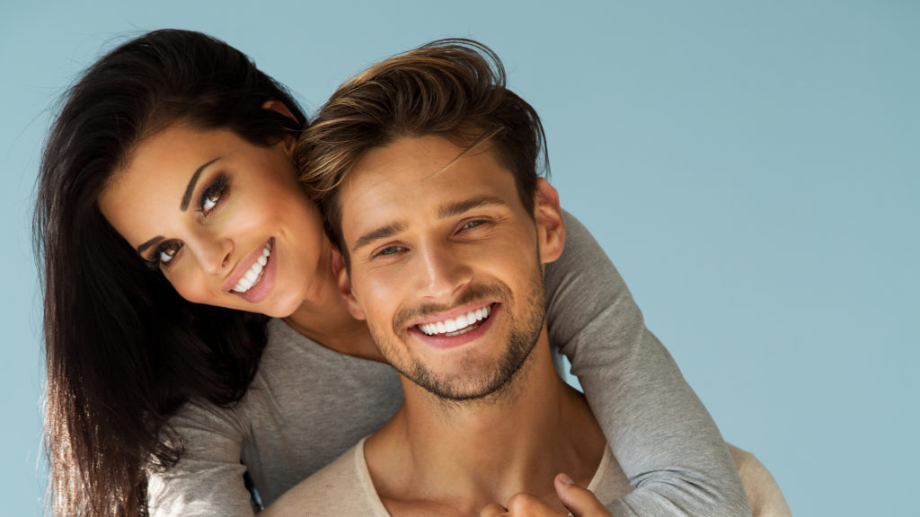young couple smiling after cosmetic dentistry